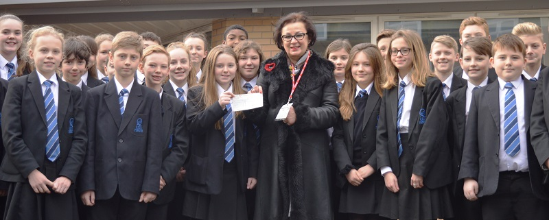 QEGS Year 7 students presenting the cheque to Marzena Harris, manager of the Penrith branch of Cancer Research UK.