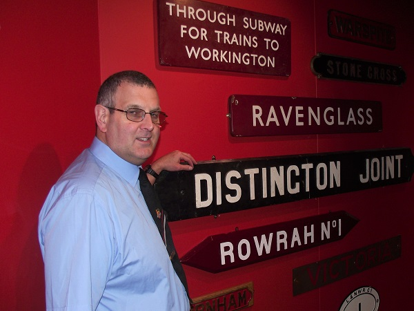 Allan Beck with a collection of salvaged signs from local stations