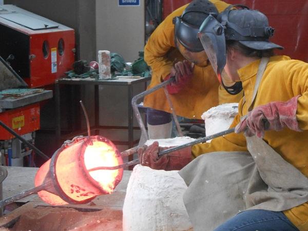 Andrea Gregson pouring bronze