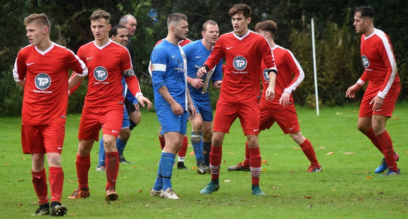 Braithwaite and Castletown players wait for an incoming free kick (Ben Challis)
