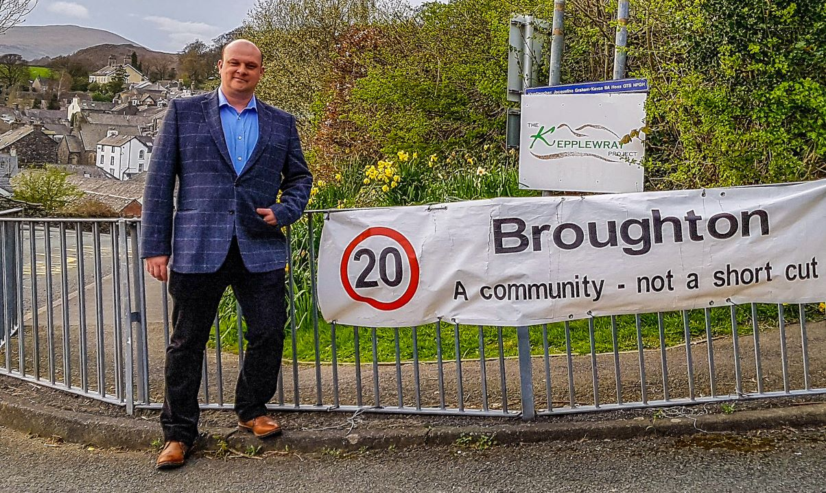 Councillor Matt Brereton poses with a Broughton speed safety sign outside the primary school