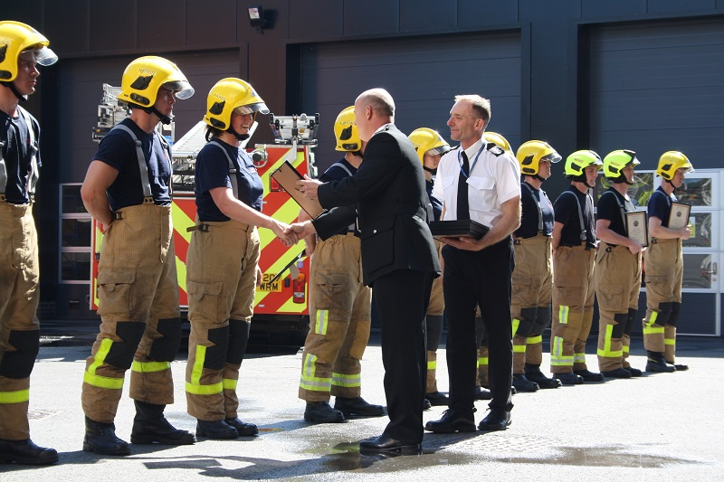 Mr Healey presents certificates to the firefighter recruits at the passing out parade.