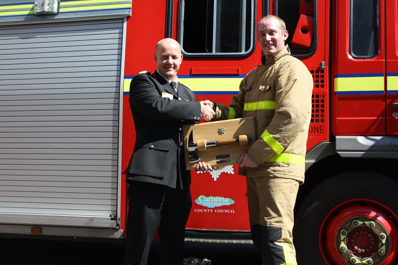 Cumbria's Deputy Chief Fire Officer Steve Healey presents the silver axe award to top firefighter recruit Michael Wardle.
