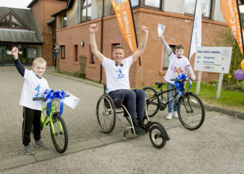 Charles Deans after he has completed his Challenge 874 which start from The Calvert Trust near Keswick arriving at Eden Valley Hospice, Durdar Road, Carlisle with Percy Harrison, six, and (right) Daniel Morris, 10, with their winning bikes; Saturday 20th March 2021