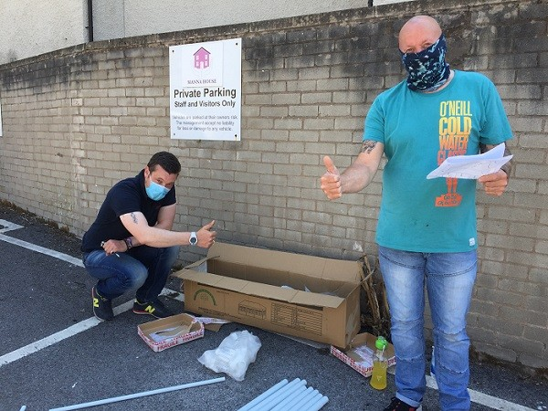 L-R: Manna House Client Support Workers Chris Holland and Chris Ryan building a gazebo for social distancing