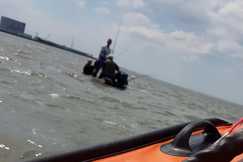 The inshore lifeboat arrives on scene to find the fisherman standing in water.