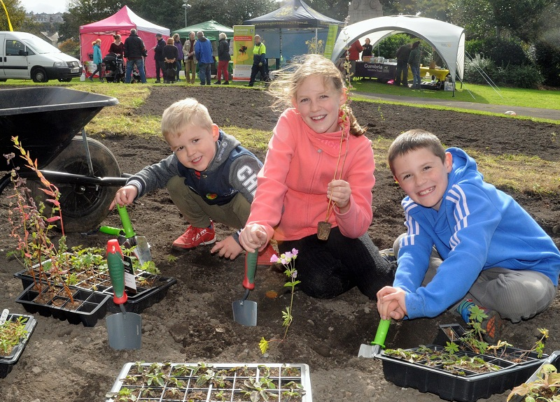 Children planting wildflowers in Vulcan Park, Workington, as part of the Get Cumbria Buzzing project © Cumbria Wildlife Trust