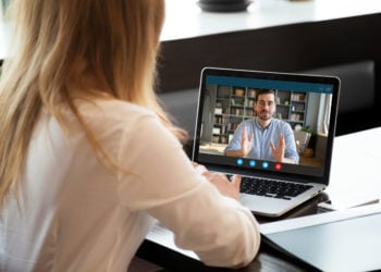 Woman looking at man on laptop