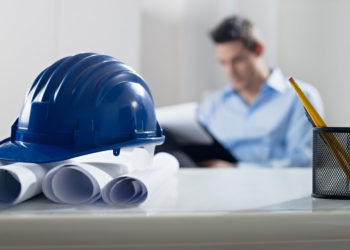 Adult,Caucasian,Male,Architect,Examining,Documents.,Focus,On,Blueprints