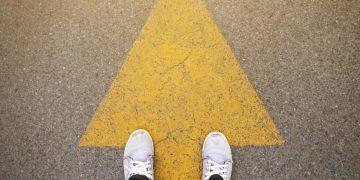 feet standing on arrow in road