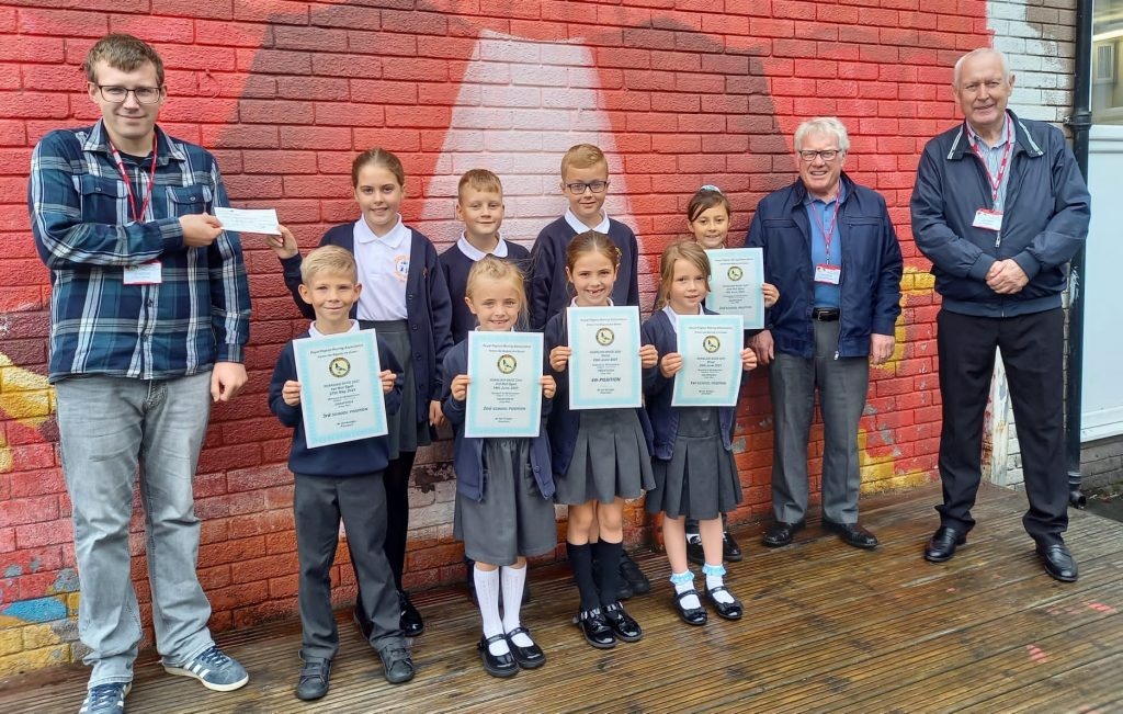 A former pupil of Frizington Primary School has gone back to present a cheque for £840 – money won by one of his pigeons.