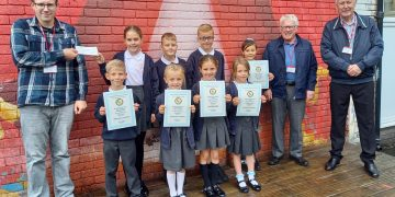 Tom Kenmare (left) with the cheque; school pupils display certificates win by Frizy Flyer in the various races alongside Cumbria Region officials Jimmy Nelson and Les Blacklock.