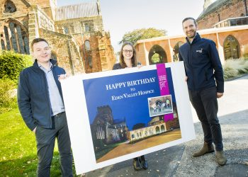 Henry Richards from Hayward Tod, (centre)  Emily Whittington from Maiden Way Group and (right) Will Tod from Hayward Tod, with the historic quarter for Eden Valley Hospice birthday card, at Carlisle Cathedral, Carlisle city centre; Wednesday 6th October 2021 JENNY WOOLGAR PHOTOGRAPHY